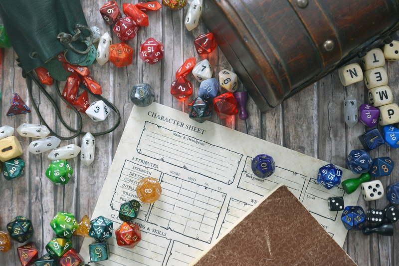 Several multicoloured polyhedral dice next to a leather bag covering an RPG character sheet